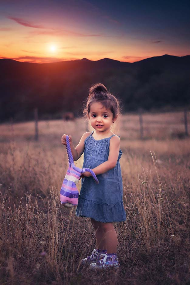 Child in field with sunset